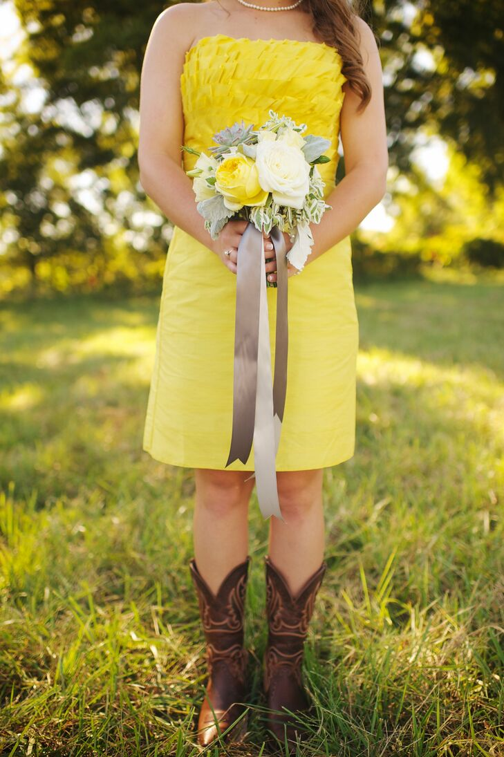 The bridesmaids carried bright bouquets of white and yellow peonies and roses, which complemented their yellow dresses perfectly. The bouquets had long satin gray and white ribbons hanging from the front.