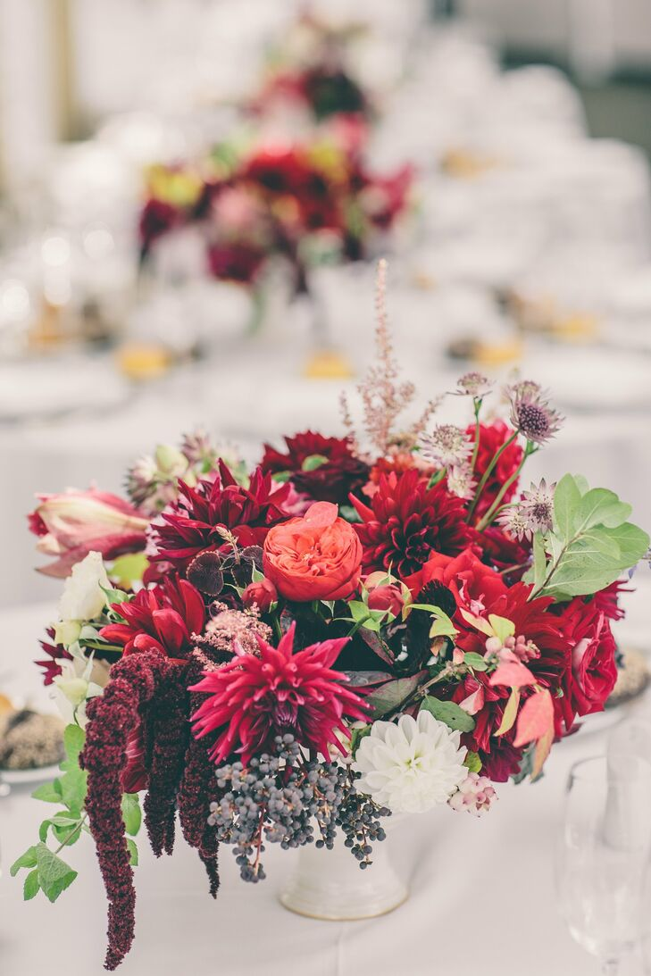 The textured centerpieces were filled with garden roses, dahlias, moss, scabiosas and leaves in rich shades of scarlet, red, orange and green.