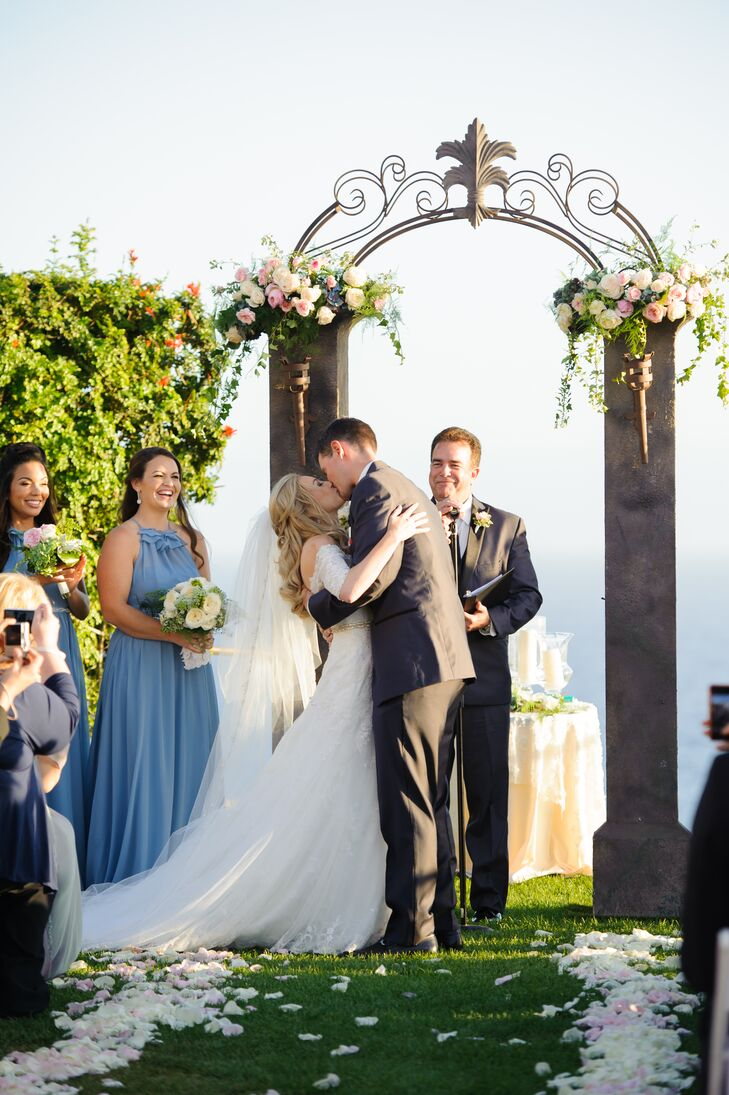 Jill and Peter shared their first kiss as a married couple during the outdoor ceremony at Trump National Golf Club in Rancho Palos Verdes, California. They kissed in front of the stone pillars with an iron arch that was accented in flower arrangements on top.