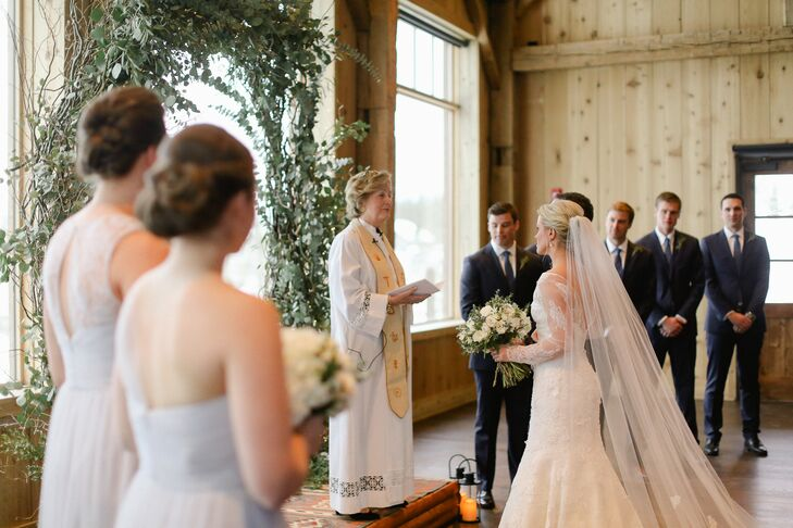 "To go with her white lace gown, Charlotte added a Sara Gabriel cathedral-length veil with lace trim on the edge. ""I wore my hair in a relaxed updo with some greenery that matched my bouquet,"" she says."
