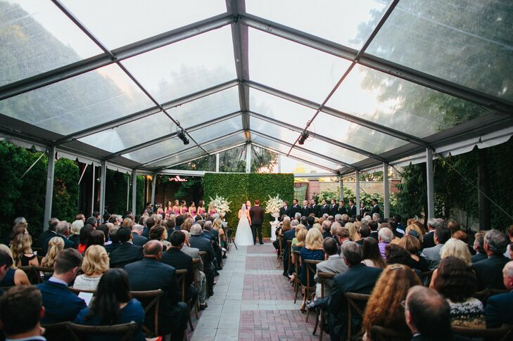 """Liz and Dave wed in an outdoor courtyard at Chicago Illuminating Company against a lush backdrop of green ivy and flanked by two large bouquets. """"I chose the venue because of the courtyard option and loved that it brought an element of the outdoor to our ceremony,"""" the bride says. Guests watched on while seated on white, wood grain chairs."""