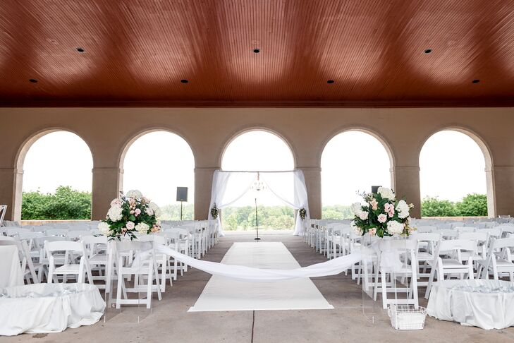 "With the pavilion at the top of a hill, Amanda hoped a slight breeze would ""react beautifully"" with the white and sheer fabric decorating the ceremony space at the World's Fair Pavilion in St. Louis, Missouri."
