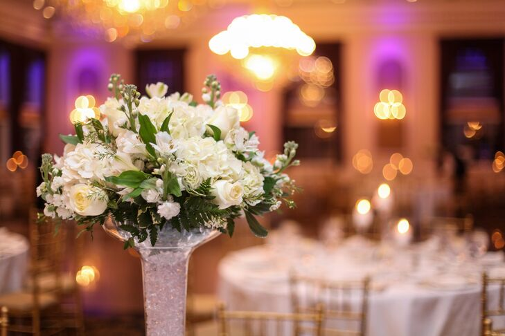 Dining tables were decorated with tall vases filled with crystals and topped with bouquets of roses, hydrangeas, lilies and stock flowers.