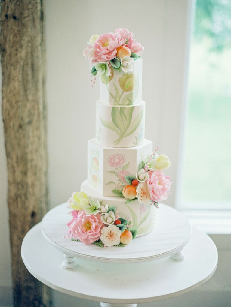 Four-tier white wedding cake with pastel botanical hand-painted art decoration
