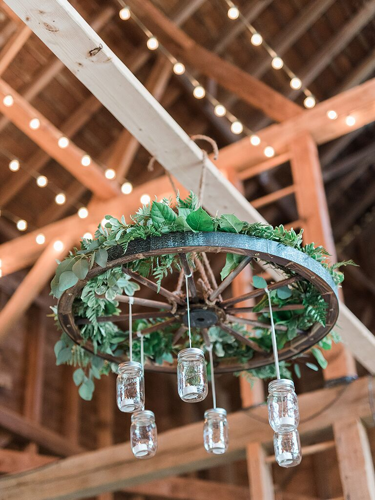 16 pretty decoration ideas for your rustic wedding wagon wheel chandelier and twinkle lights for a rustic barn wedding idea arubaitofo Image collections