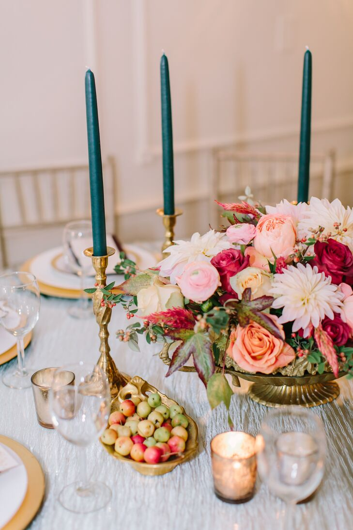 Having different centerpieces for each table was a must for Stefanie, and the couple's planner, Jackie, didn't disappoint. Bright pink, peach and burgundy blooms were styled alongside fresh fruit, vintage brass candlesticks and various vintage bits and pieces to create a dramatic look that exuded old-world elegance.