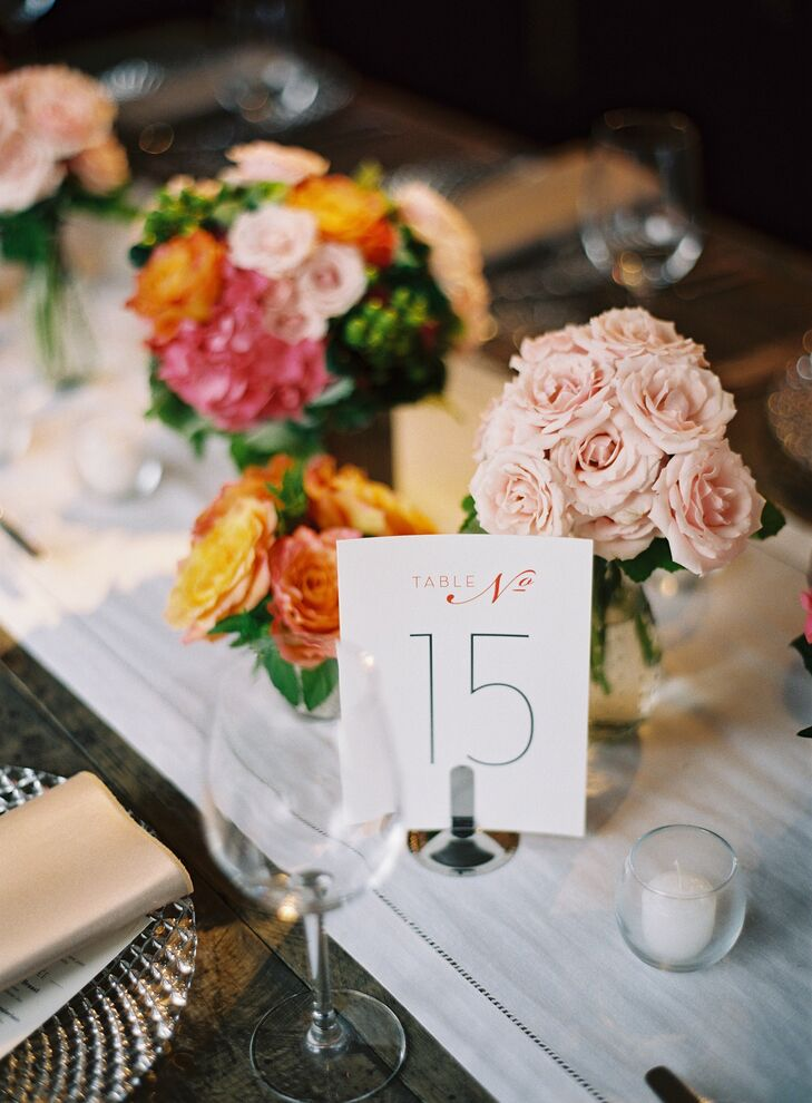 The table number cards were placed in between small pink, coral and tangerine rose centerpieces.