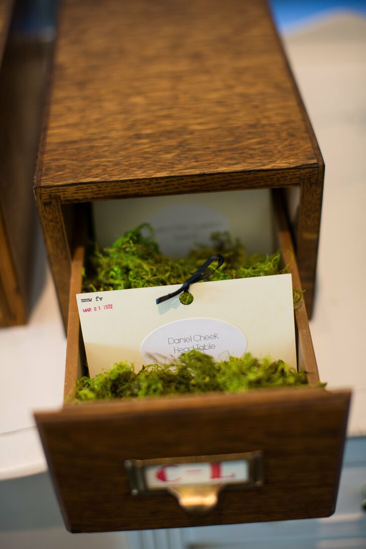 A vintage card catalog held the escort cards, which sat on a bed of moss and were filed away in alphabetical order.