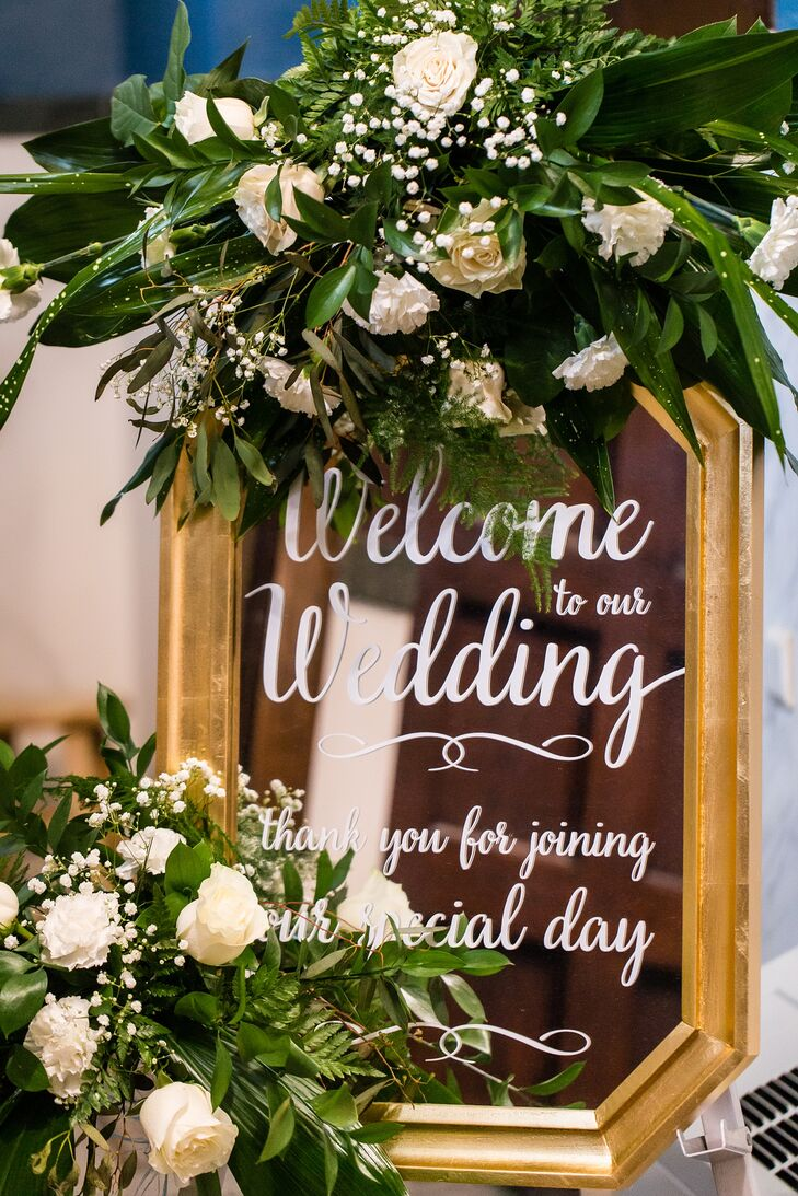 For the ceremony decor at St. Cecilia Catholic Church in St. Louis, Missouri, Whitley and Carlo added only black lanterns on both sides of the aisle, a gold welcome sign and two floral arrangements outside.