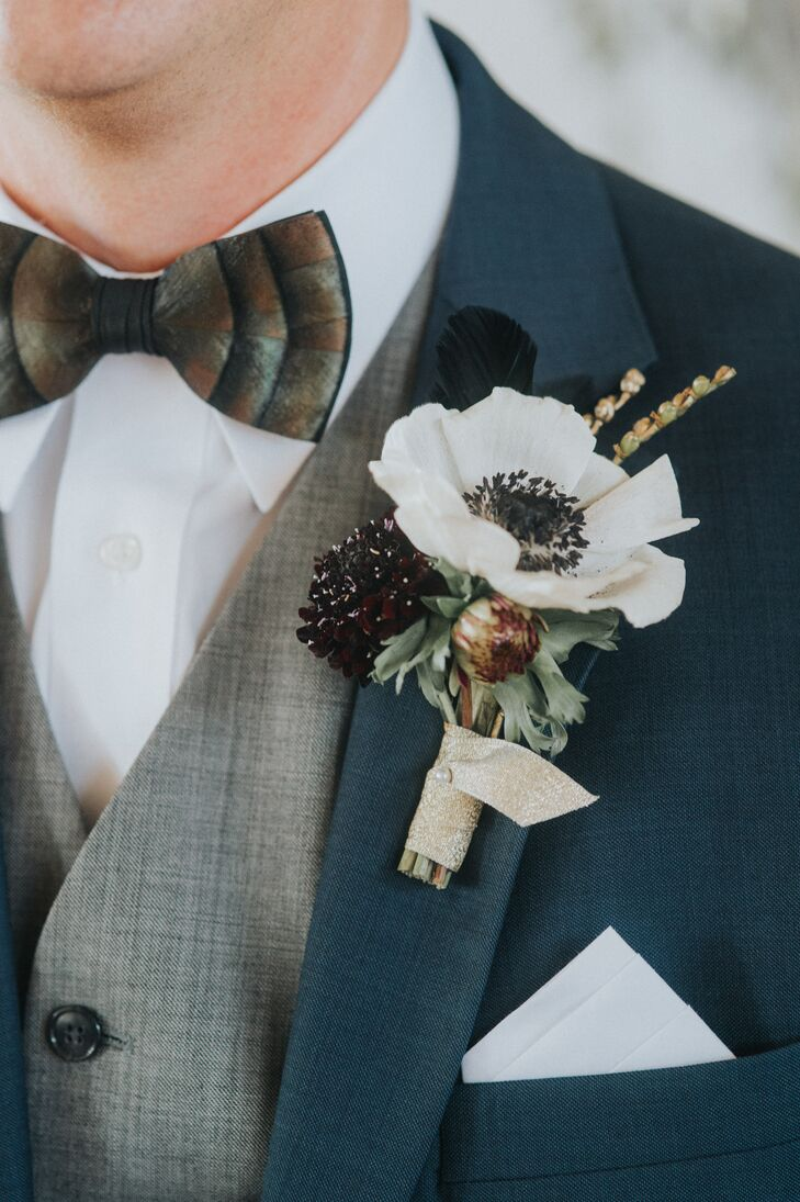 Autumnal-colored blooms and greenery were incorporated into boutonnieres and tied with a gold ribbon.