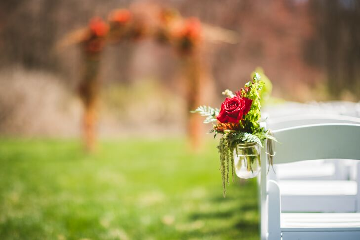 The same flowers picked for their centerpieces, bouquets and boutonnieres were used in the aisle decor. Lush arrangements of red roses, orange proteas and greenery were placed in mason jars and hung against each row of white folding chairs.