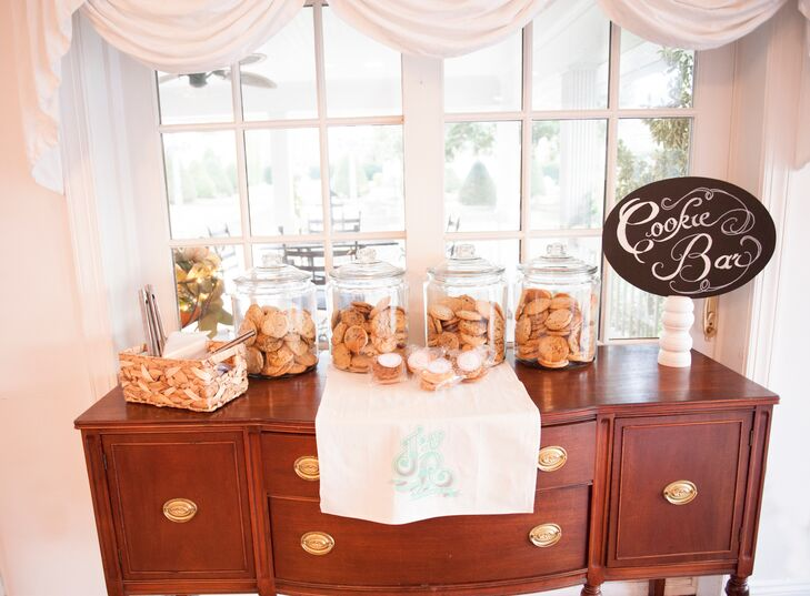 Jo and Robert had a cookie table for dessert. The cookies, made by Jo's mom, were displayed in glass jars on a vintage bureau. The table was labeled with a hand-painted sign. They also had a pie table in addition to the wedding cake and groom's cake.
