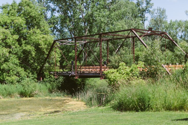 Megan and Carson had their ceremony on top of a iron bridge at Givens Farm in Hortonville, Wisconsin. Guests sat in wooden chairs arranged in rows to watch Megan and Carson get married.
