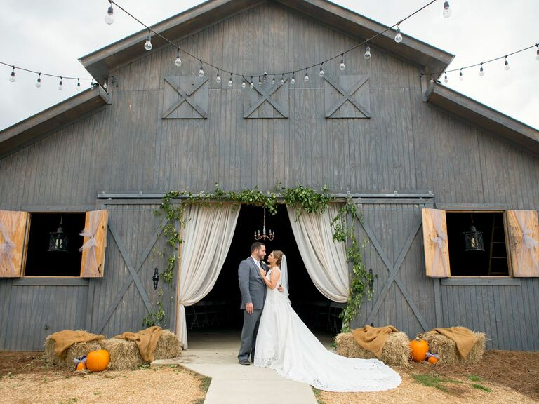 Newlyweds in front of rustic barn