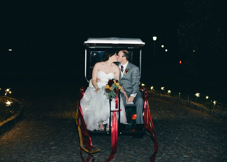 Ellie and Adam made their exit on the back of a golf cart decked out in red and gold ribbons that complemented the wedding's color scheme.