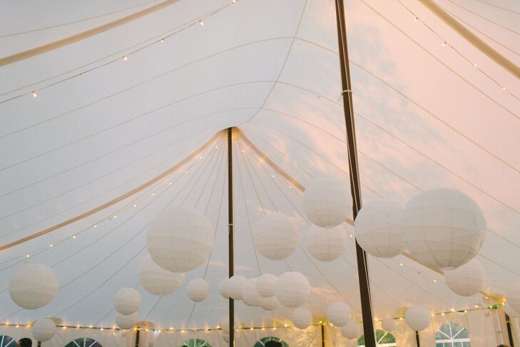 An array of white paper lanterns made up interesting lighting at the top of the pitched reception tent. A good replacement for the typical chandelier.