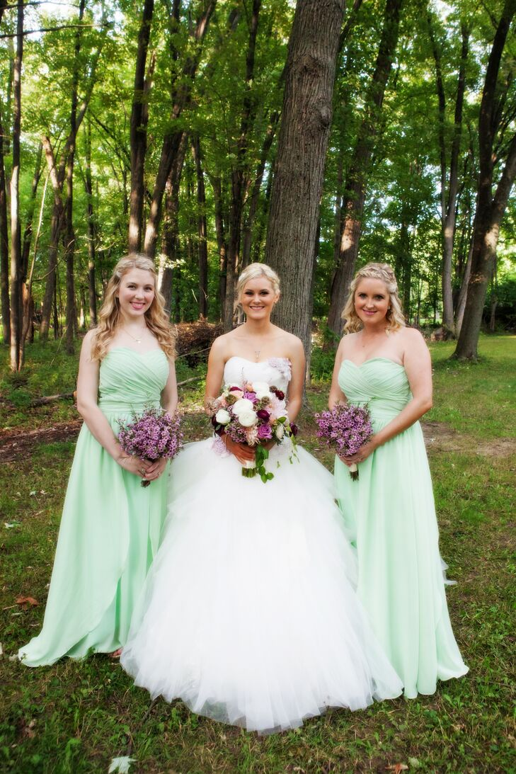 Bridesmaids wore strapless, floor-length mint dresses with a champagne-colored heel. Each carried a bouquet of purple wax flowers at the couple's wedding in Rochester Hills, Michigan.