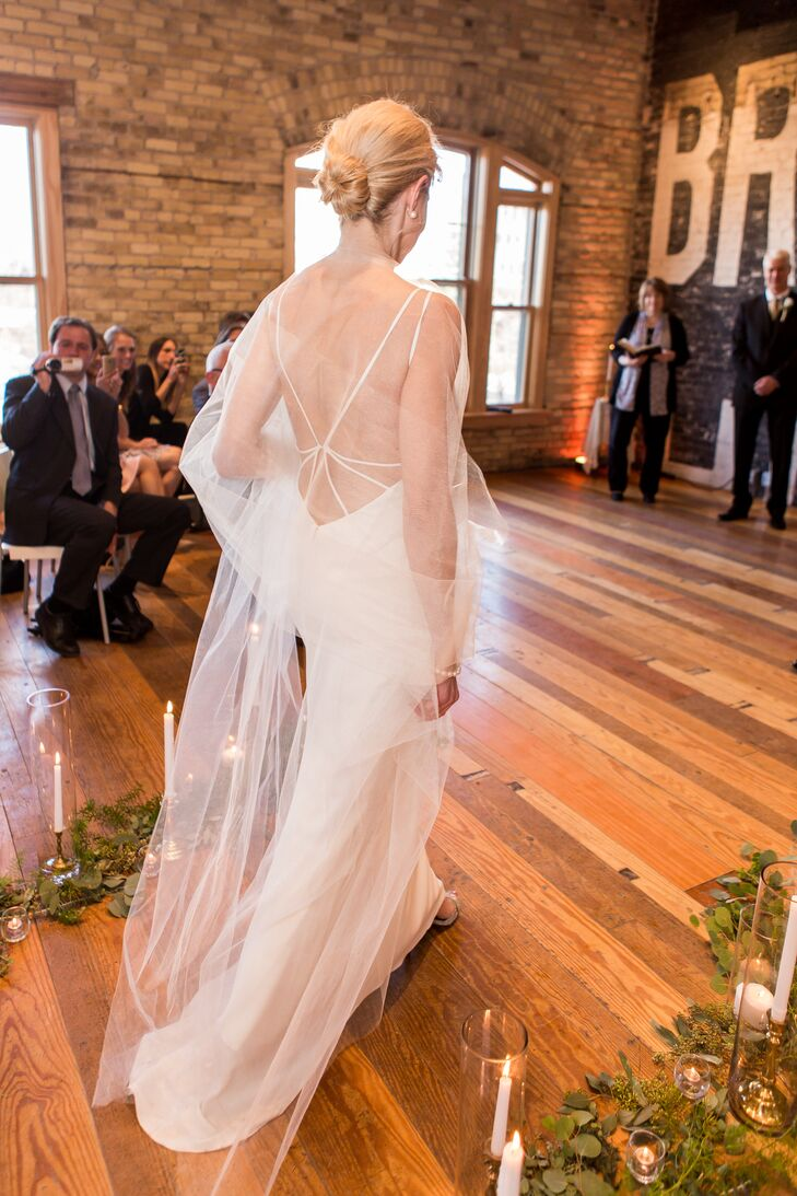Katherine's gown featured delicate straps and an open back. She wore a sheer shawl. The aisle was lined with eucalyptus leaves, tree branches and candles.