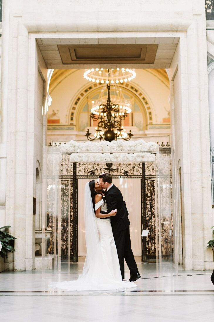Classic First Kiss in Front of Acrylic Wedding Arch Covered with White Flowers