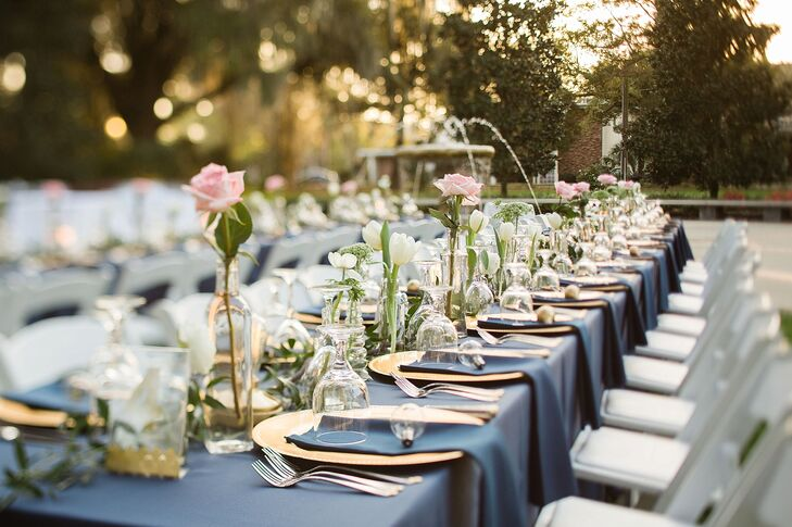 Designed by the Flower Shop, tablescapes of pink roses, white tulips and greenery lined family-style tables in clear-glass bulb vases for a simple and sweet touch. DIY Edison lightbulbs also accented the arrangements with a bit of vintage flair.