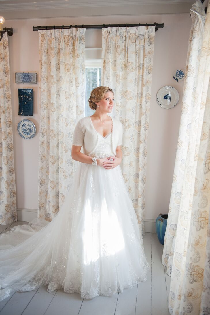 """Though a ball gown was the last thing Jill envisioned for her walk down the aisle, a classic full-skirted dress with elegant lace appliques and a sweetheart neckline eventually won her over. """"The dress seemed like it would fit in with the wedding venue, whereas a more fitted gown could end up feeling too formal and out of place,"""" Jill says. To keep warm during their outdoor """"I dos,"""" Jill completed her look with a soft ivory cover-up."""