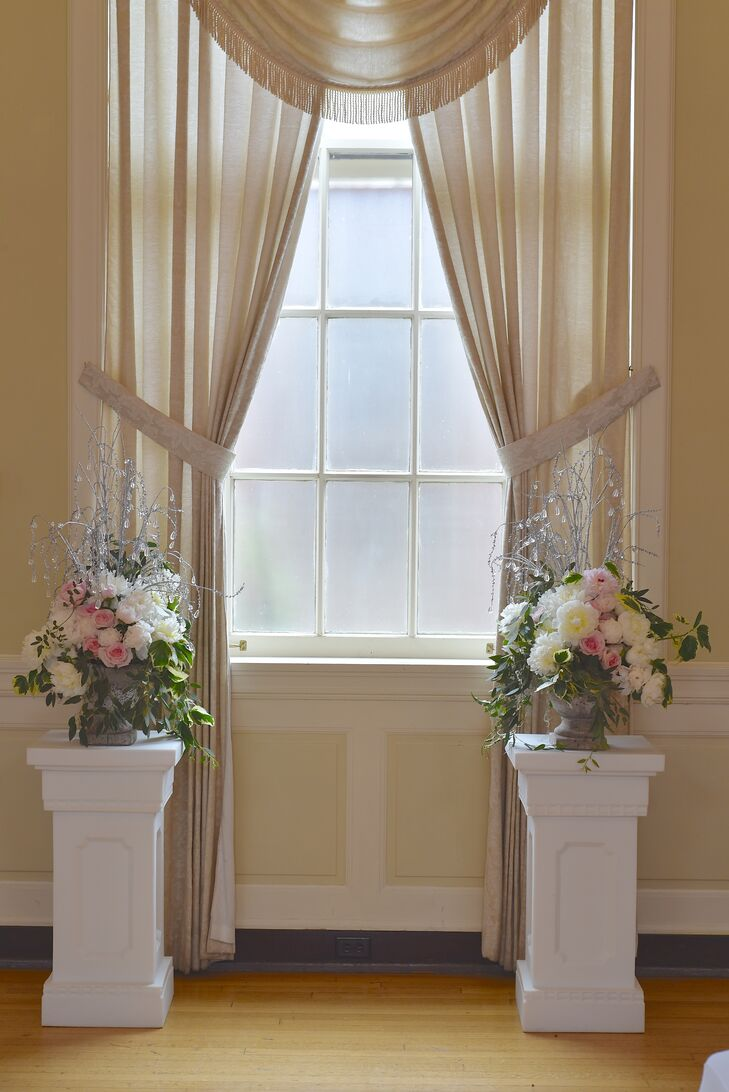 The altar area where Erika and Ralph were married was flanked by white pillars that featured pastel flower arrangements. These flower arrangements included white peonies, pink roses, greens and crystal accents.