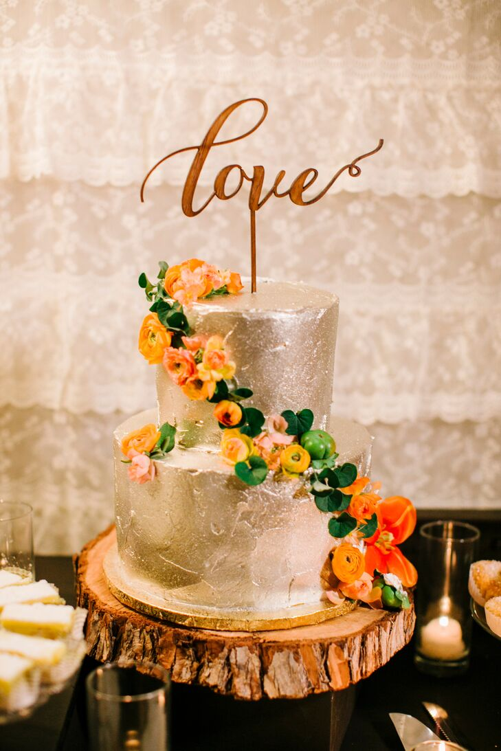 "The two-tier white wedding cake filled with raspberry had an iced surface that glistened with beauty. The dessert had colorful blooms wrapped around its layers with a wooden ""Love"" topper."