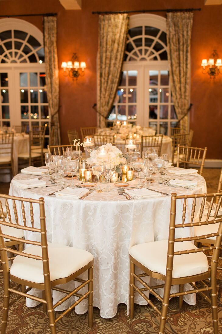 Building on the room's rustic amber walls and golden curtains, the couple highlighted every reception table in gold and white decor. White hydrangea centerpieces and gold votives stood out atop a mirror charger and white linens with scroll detailing. Gold chiavari chairs surrounded every one for a dramatic contrast.