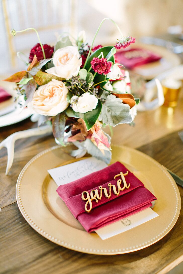 "Each place setting featured a custom individual laser-cut name, a gold charger, a wine-colored linen napkin and a menu inscribed with the message ""Let's feast with thankful hearts."""