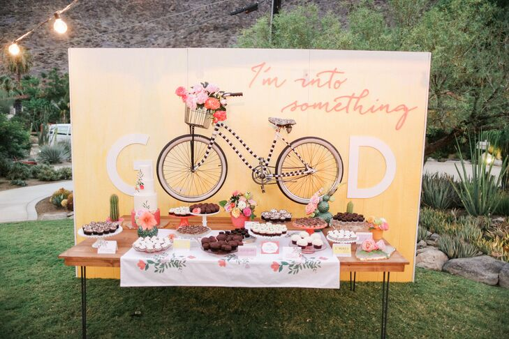 "An actual beach cruiser was hung on the backdrop for the dessert table, which read ""I'm into something good"" and offered nearly a dozen different sweets, including cookie bars and cupcakes."