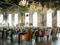 Vintage wedding reception with antique chandeliers, mismatched velvet chairs, candlesticks and string lights