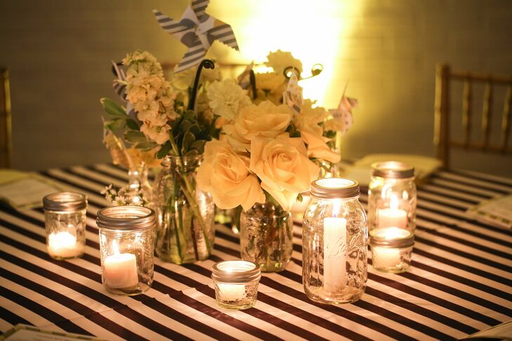 Black-and-white striped tablecloths and Mason jars filled with flowers and candles perfectly embodied the couple's vintage carnival theme.
