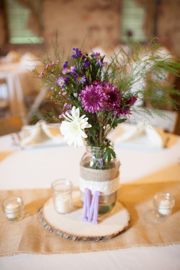 Sara and Josh's centerpieces were simple, with mason jars of chrysanthemums and wildflowers arranged on wooden slabs.