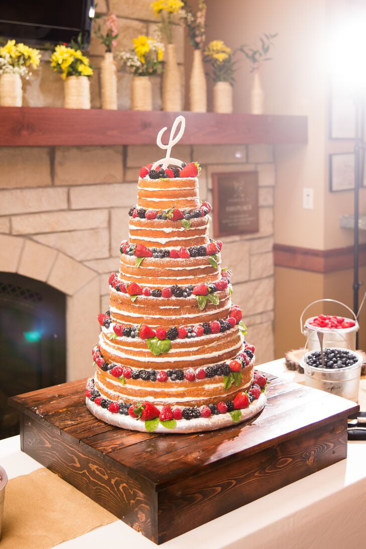 The bride and groom cut into a luscious six-tier naked cake to celebrate their nuptials. The confection sat atop a DIY wooden cake stand. A monogram topper crowned the dessert. Extra berries sat in pails waiting to further accompany each guest's slice of cake.