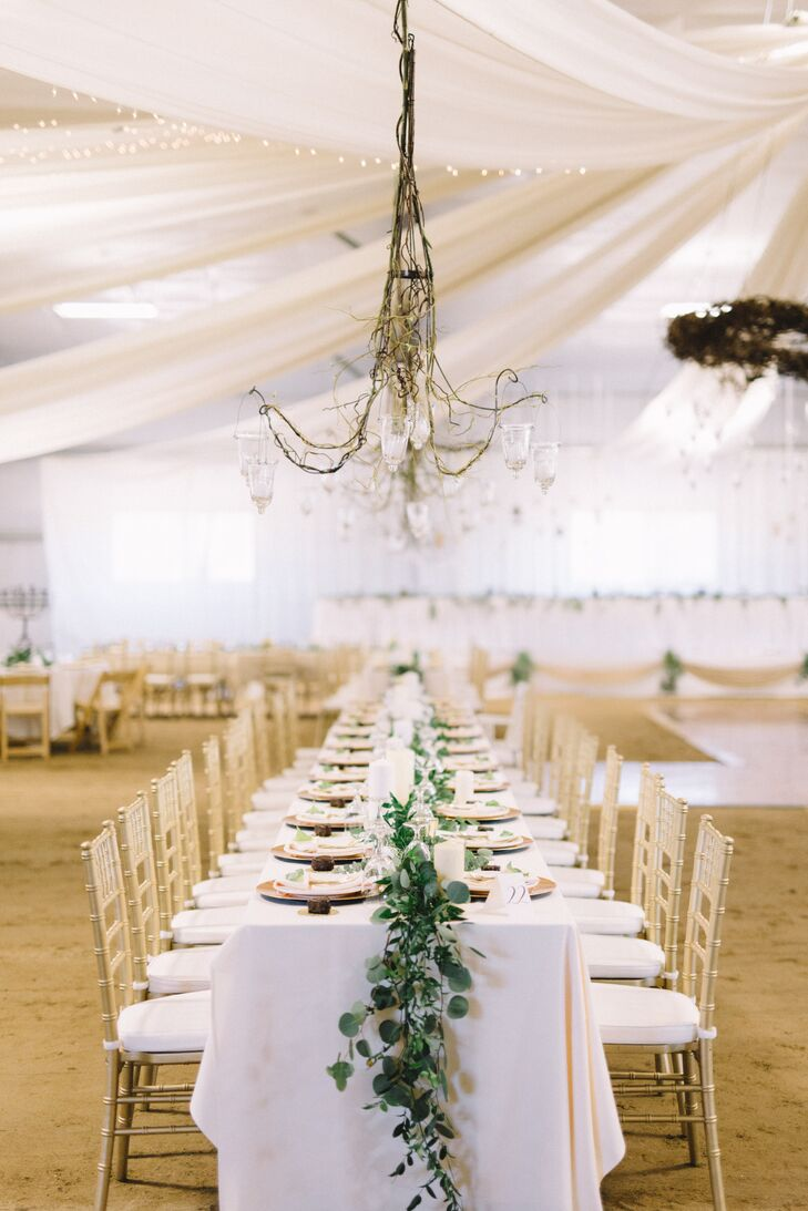Fabric was draped over the arena to transform and soften the large steel building. Ten chandelier armatures, decorated with glowing candles, hung over long farm tables on both sides of the aisle.