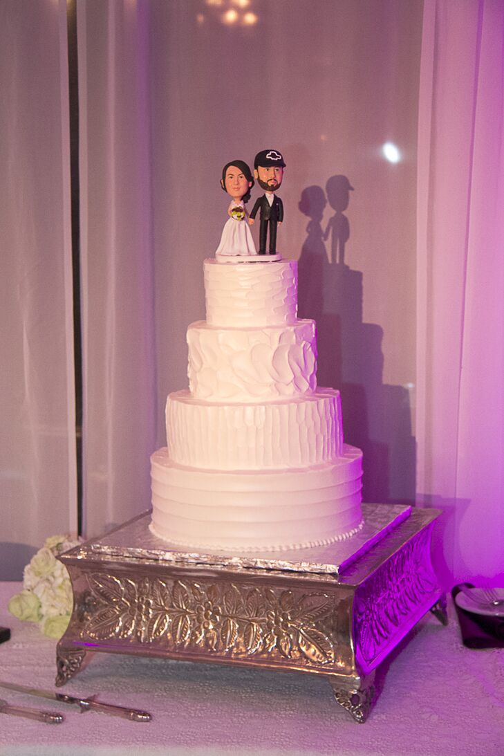 The four-tier white wedding cake had four different flavors: red velvet, double chocolate, lemon curd and raspberries, and carrot cake. It was decorated with a caricature bride and groom cake topper to showcase the couple's whimsical personalities.