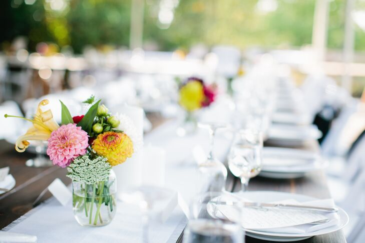 Small colorful flower arrangements of dahlias and lilies accented with Queen Anne's lace decorated the long dining tables.