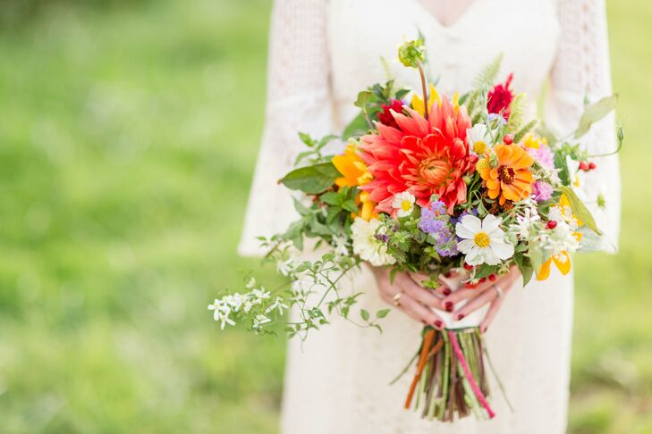 """The bridal bouquet made up of colorful blooms and accents of greenery created a bold statement against Carlyn's ivory wedding dress. """"When I met with Tara, who made the bouquets, I told her I loved wildflowers, daisies, greenery and bright colors,"""" Carlyn says. """"She took those ideas and made the most incredible bouquets ever."""""""
