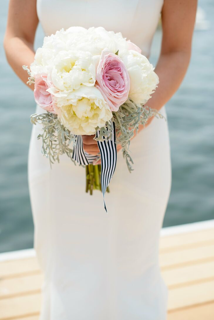 A black-and-white-striped ribbon wrapped Clare's bouquet of peonies, roses, hydrangeas and carnations.