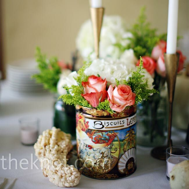 For the centerpieces, Megan found some vintage tins at Goodwill and filled them with coral roses and hydrangeas. The bride's aunt added a variety of gold candlesticks to the display.