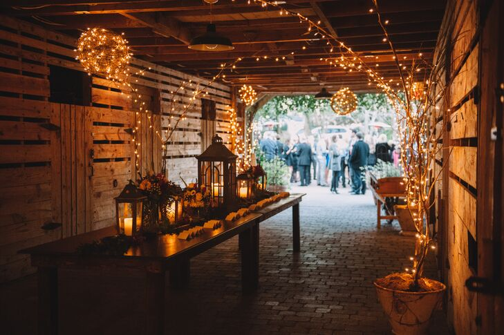The entryway into the rustic barn was decorated with trees and grapevine balls adorned with string lights. In the center, two tables held black lanterns filled with pillar candles to add plenty of rustic romance to the escort card table.
