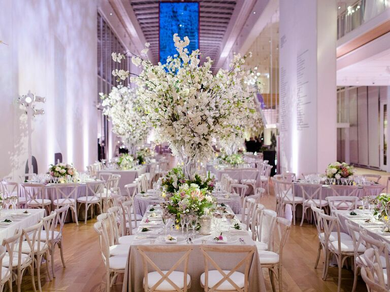 Glamorous wedding reception in art institute with lavish white floral centerpieces