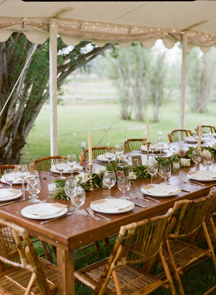 White and blush flowers tucked into a seeded eucalyptus garland down the center of the natural wood farm tables, adding an overgrown garden aura to the reception. Chutney and Steve added plenty of romance to the tent, with candlelight from antique brass candlesticks scattered on the tables.