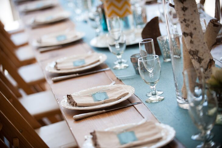 Nicole blended her vintage vision with homespun details with her reception place settings. Wooden tables were set with white china and topped with canvas napkins with rustic, exposed seams.
