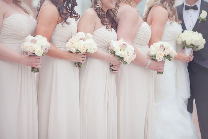 Megan's bridesmaids wore strapless, floor-length dresses in champagne and carried bouquets with blush and ivory roses.