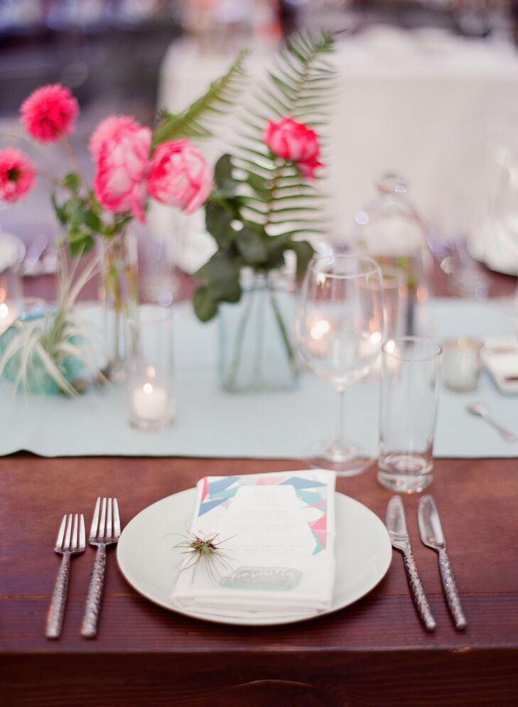 At each setting, soft green plates provided a neutral backdrop for colorful pink centerpieces, tiny terrariums and geometric-patterned menus.