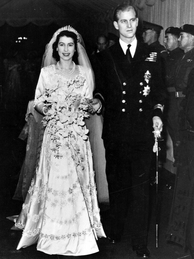 Queen Elizabeth wedding picture with Prince Phillip walking through church on wedding day