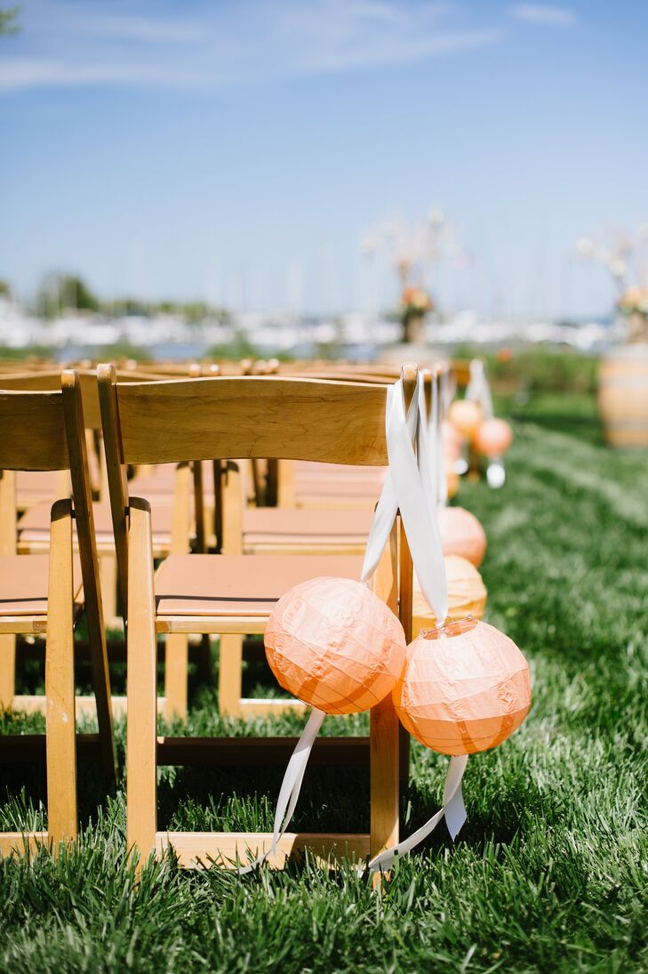 The couple kept the ceremony decor simple, opting for orange paper lanterns along the aisle and flower-topped wine barrels at the altar.
