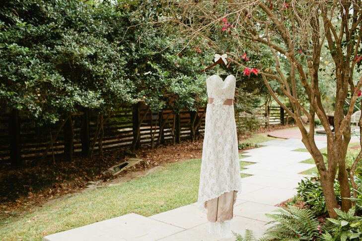 The bride wore a lace wedding dress with a champagne-colored underlay and a sweetheart neckline. She accessorized her simple, classic dress with a mauve belt, which matched the colors of the wedding party.