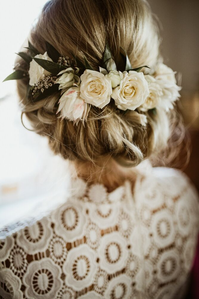 """One of my bridesmaids owns a salon and is the best stylist on the planet. She did my hair, and her talented team took care of the rest of the ladies,"" Laura says of her wedding day hair, which was accented with fresh flowers."